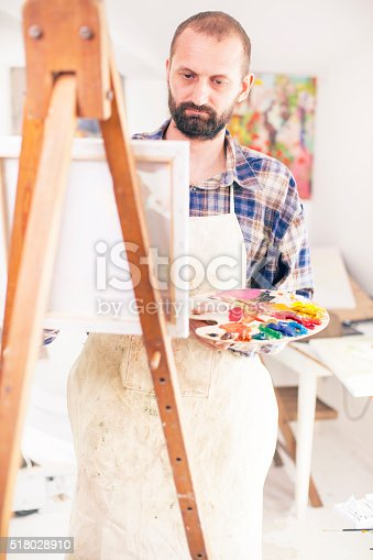 istock Concentrated painter working at his studio 518028910