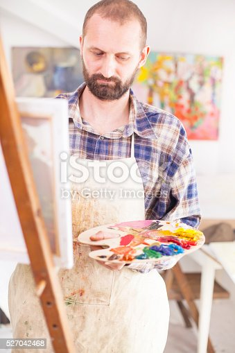 istock Concentrated painter working at his studio-close up 527042468