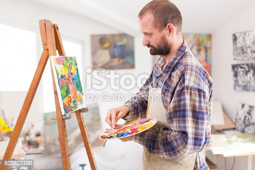istock Concentrated painter working at his studio-side view 523827100