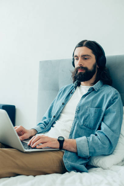 Concentrated person using his modern laptop for work stock photo