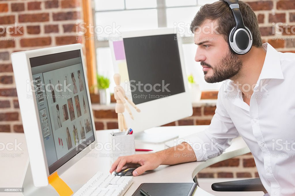 Concentrated photo editor using computer in office stock photo