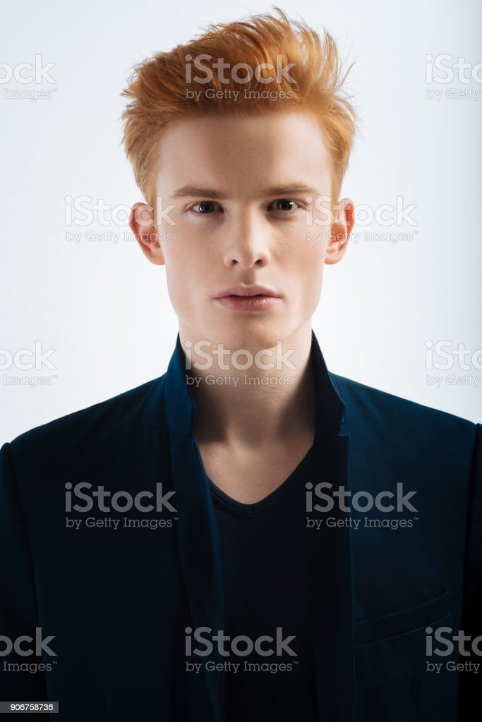 Concentrated red-headed young man staring stock photo