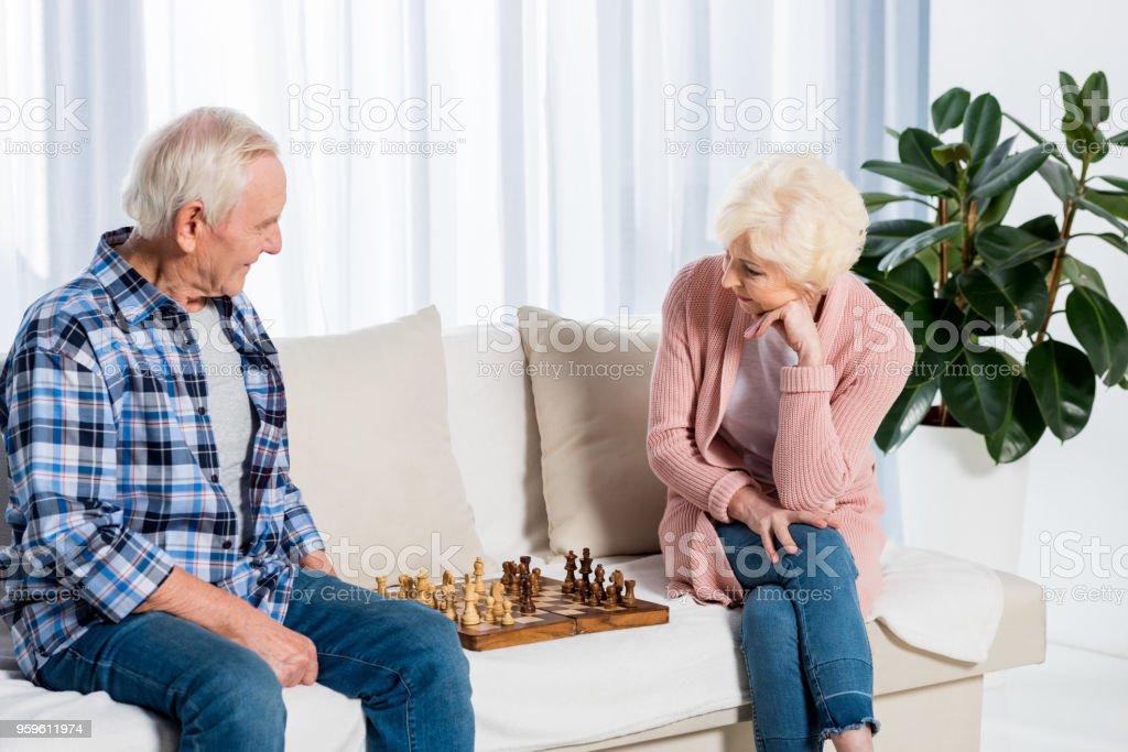 concentrado senior pareja jugando al ajedrez en casa en el sofá - Foto de stock de Acogedor libre de derechos