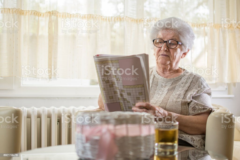 Concentrated senior woman doing some crossword at home. stock photo