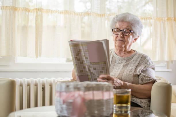 konzentrierte senior frau einige kreuzworträtsel zu hause zu tun. - kreuzworträtsel lexikon stock-fotos und bilder