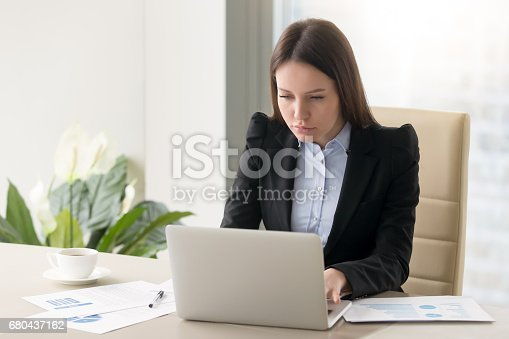 istock Concentrated serious businesswoman making report, working with laptop in office 680437162