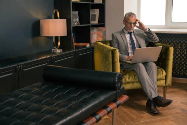 Konzentrierter grauhaariger Mann sitzt in einem Sessel – Foto