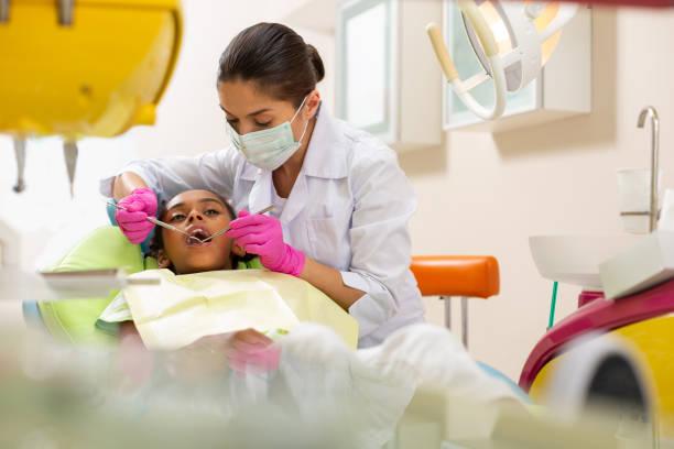 Konzentrierte sserious mittleren Alter Ärztin mit zahnärztlichen Instrumenten – Foto