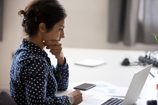 istock Concentrated serious office worker millennial woman analysing results 1124997372