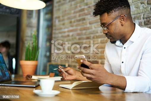 istock Concentrated skilled afro american administrative manager of restaurant sitting in food court dialing number from visit card planning to arrange meeting with journalist to publish advertising content 908015256