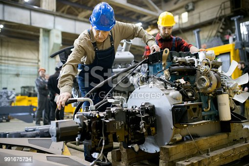 Skilled engineers assembling tractor engine