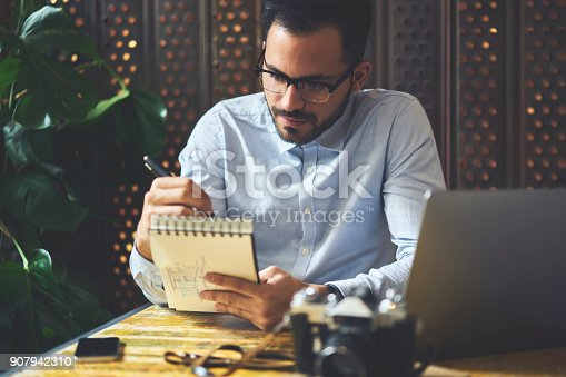 Concentrated skilled graphic designer pondering while drawing sketch for project analyzing information and accountings sitting in cafe interior, prosperous businessman writing in notepad making plan