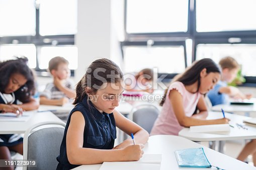 istock Concentrated small school children sitting at the desk in classroom, writing. 1191273919