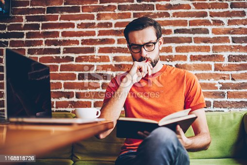 1174436608 istock photo Concentrated smart hipster student learning information from textbook preparing for seminar.Pensive young man thinking on studying task sitting in coworking at table with modern netbook 1168818726