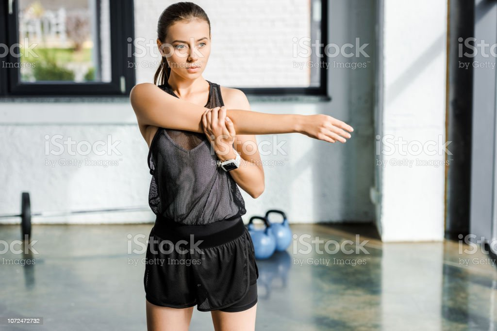 concentrated sportswoman doing stretching exercise before training session at fitness studio