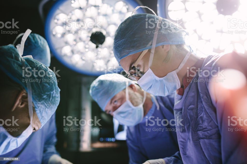Concentrated surgeon performing surgery with her team stock photo