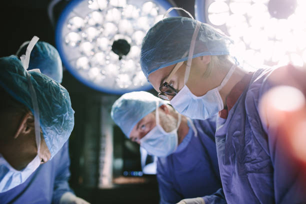 Concentrated surgeon performing surgery with her team Concentrated female surgeon performing surgery with her team in hospital operating room. Medics during surgery in operation theater. medical procedure stock pictures, royalty-free photos & images