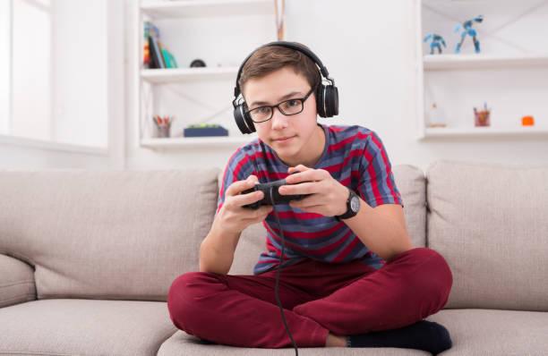 自宅でビデオ ゲームをプレイ 10 代の少年を集中してください。 - ゲーム ヘッドフォン ストックフォトと画像