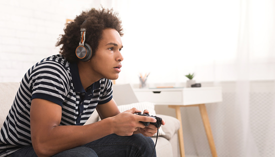 istock Concentrated teenager playing video games with joystick 1080967182