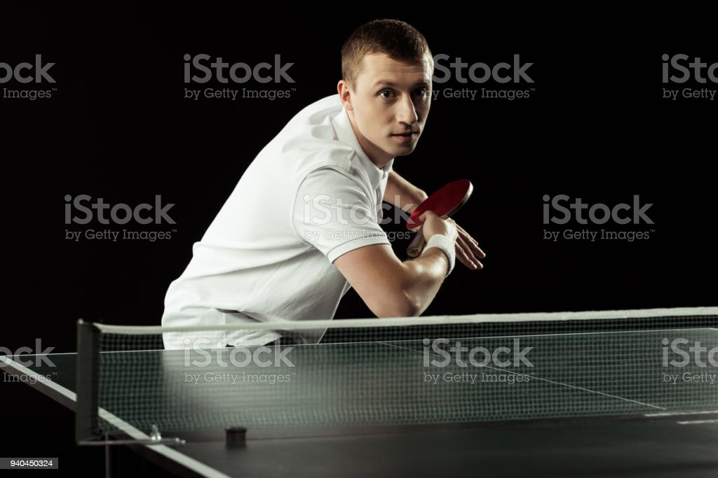 concentrated tennis player playing table tennis isolated on black