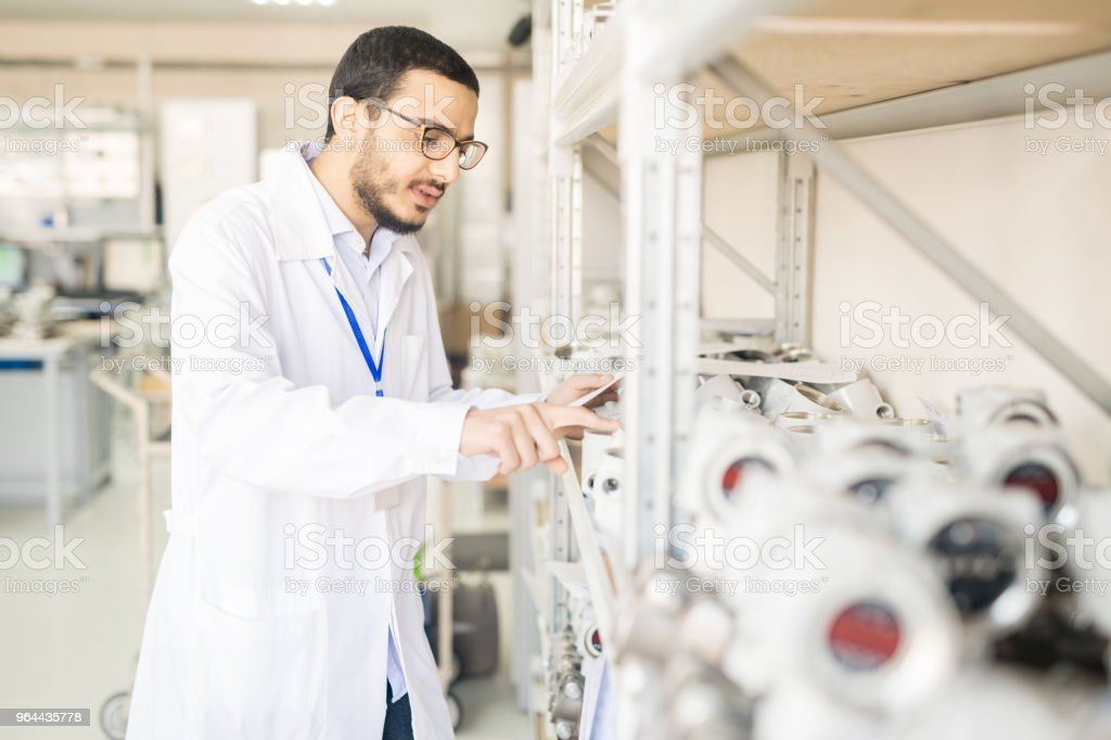 Concentrated test engineer examining pressure sensors - Royalty-free Adult Stock Photo