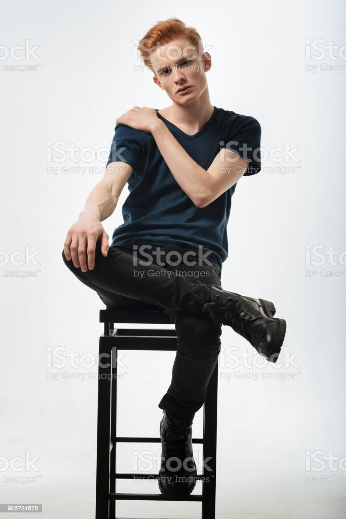 Concentrated well-built young man sitting on the chair stock photo