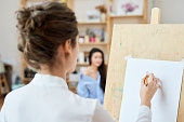 Rear view of female artist drawing posing model in modern workshop, woman using pencil to draw on paper
