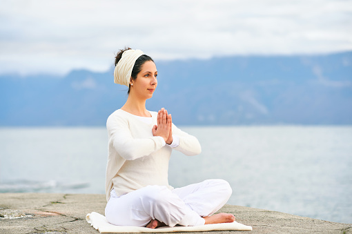 Concentrated woman meditating by the sea or lake, wearing white clothes