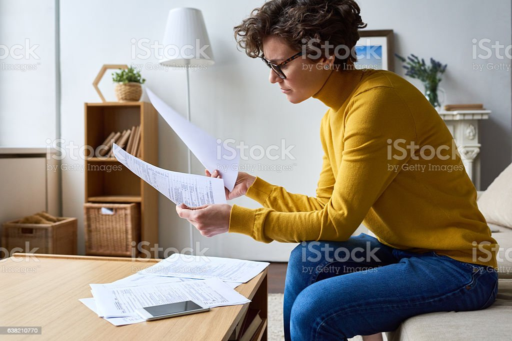 Concentrated woman reviewing financial documents at home stock photo