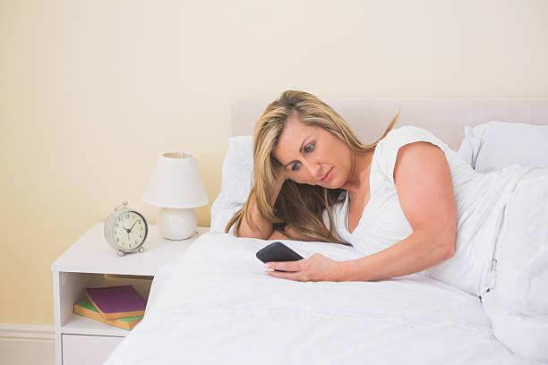 konzentrierte frau mit handy auf ihrem bett liegen - nachttischleuchte touch stock-fotos und bilder