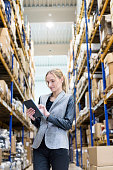 Vertical color image of confident young woman supervisor holding and touching digital tablet in warehouse. Young blond woman standing at distribution warehouse and wearing elegant suit. Industrial boss sincerely smiling and looking at camera. Logistic worker working in a large distribution warehouse. Large distribution storage in background with racks and shelfs full of packages, boxes, pallets and crates ready to be delivered. Logistics, freight, shipping, receiving.