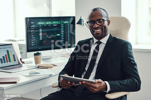 Concentrated young African man in formalwear using modern technologies and smiling while working in the office