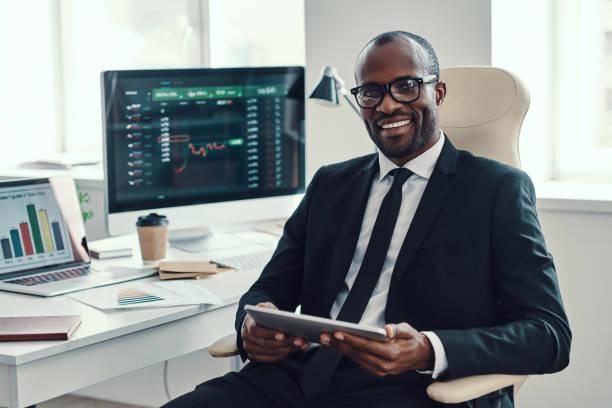 フォーマルウェアに集中した若いアフリカ人男性 - 投資家 ストックフォトと画像