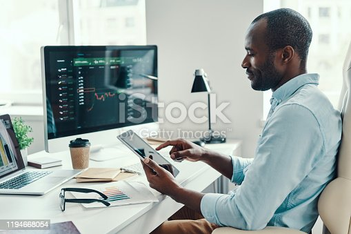 Concentrated young African man in shirt using digital tablet while working in the office