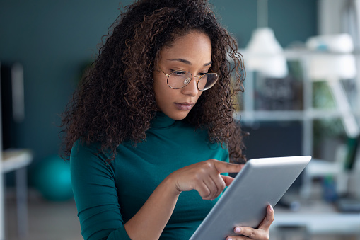 Portrait of concentrated young entrepreneur woman using her digital tablet while standing in the office.