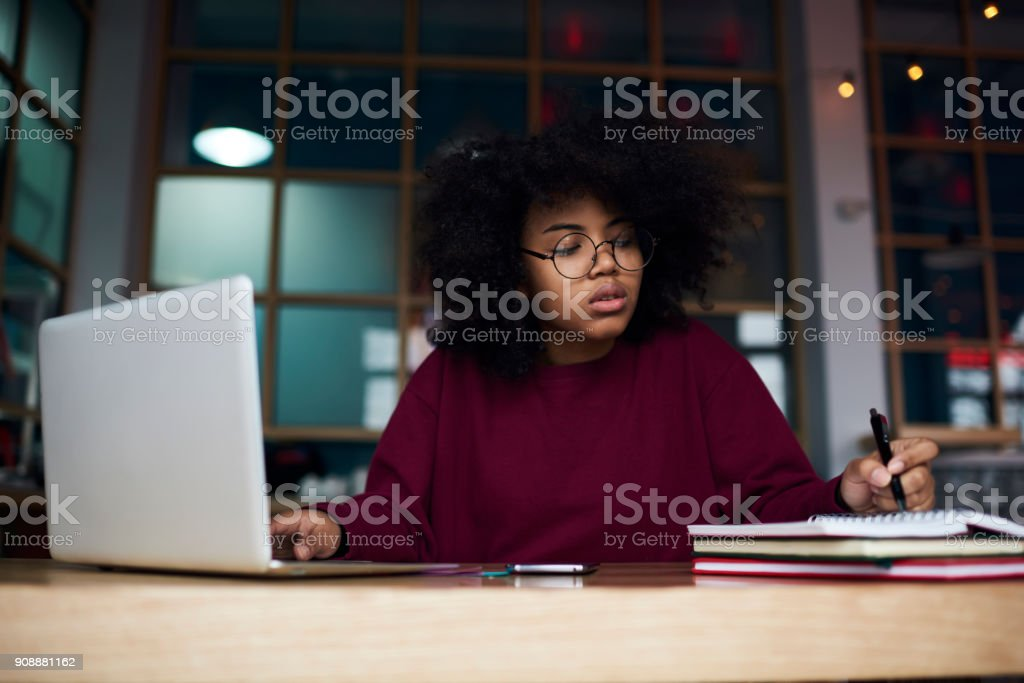 Concentrated young female student in glasses learning in university campus using laptop computer and wireless connection to internet preparing to examination, attractive hipster girl writing essay stock photo