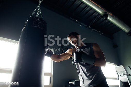 Concentrated young man box training by himself in the gym.