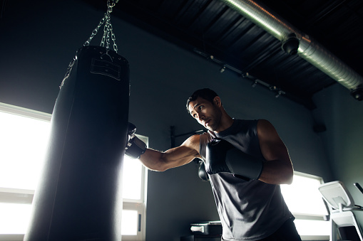 istock Concentrated young man box training in the gym 1130300402
