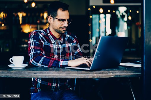 Concentrated young man copywriter in stylish eyeglasses keyboarding information on modern laptop computer sitting in coffee shop interior.Male graphic designer working freelance at digital netbook