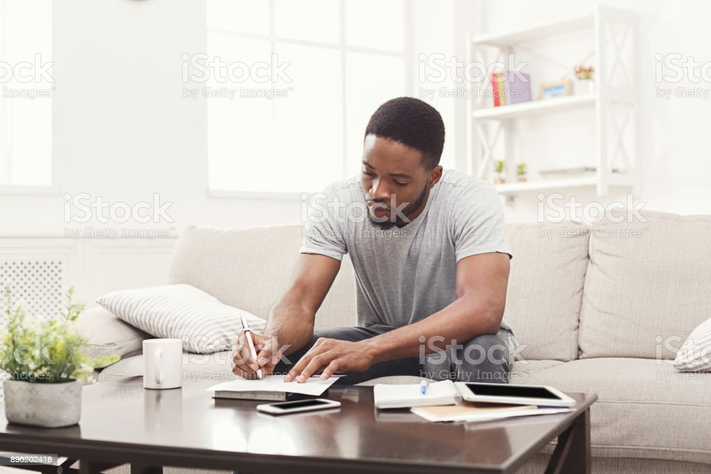 Concentrated young man preparing for exams at home stock photo