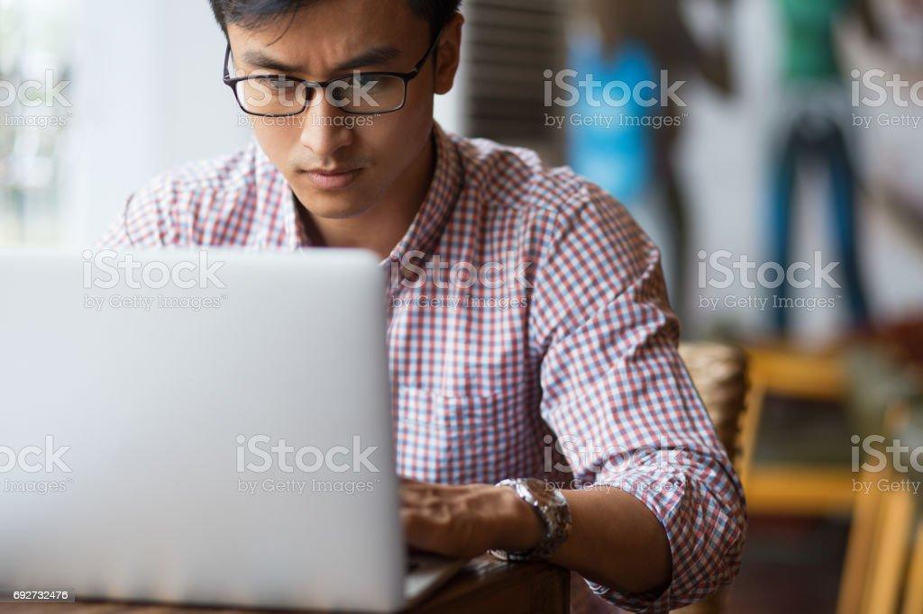 集中在咖啡館在筆記本電腦上打字的年輕人圖像檔