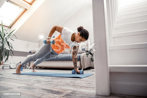 Lady using dumbbells. Concentrated young sportive woman rising hands with dumbbells while making plank on yoga mat