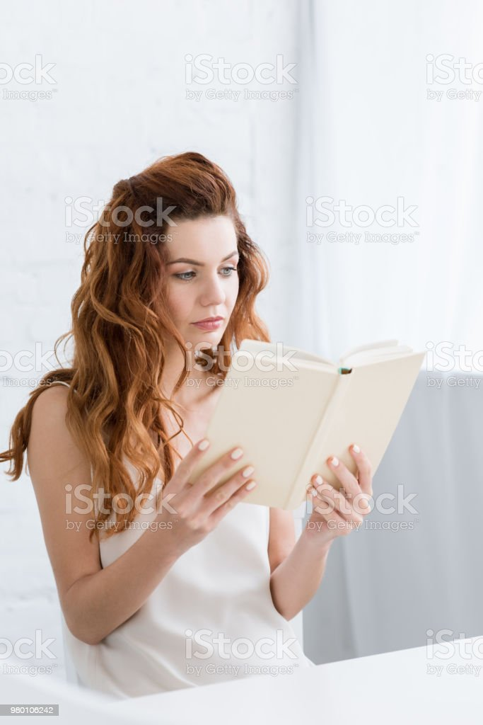 concentrated young woman reading book at home stock photo