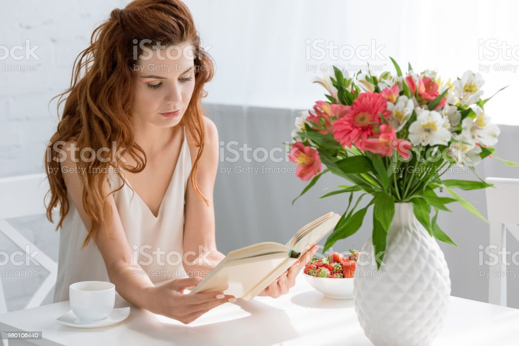 concentrated young woman reading book while sitting at table with coffee cup and flowers in vase stock photo
