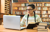 Attractive young woman with braids and eyeglasses, holding a book and working on laptop. Bookshelves as background. Stack of books on desk.