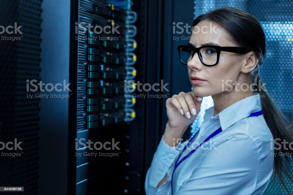 Concentrated young woman working in a data center stock photo