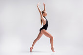 Serious young sport woman is standing on toes in lunge pose and keeping hands up