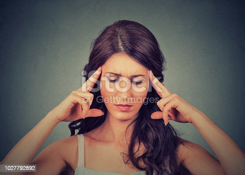istock Concentrating beautiful woman holding fingers on temples 1027792892