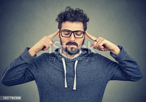 istock Concentrating businessman holding fingers on temples 1027792306
