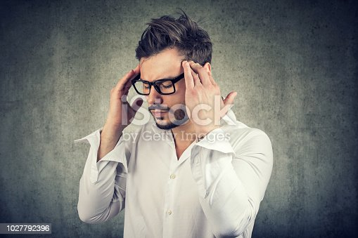 istock Concentrating businessman holding fingers on temples 1027792396